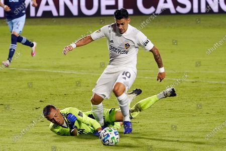 Vancouver Whitecaps goalkeeper Evan Bush, bottom, stops a shot from Los Angeles Galaxy's Cristian Pavon (10) during the first half of an MLS soccer match, in Carson, Calif