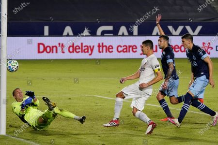 Vancouver Whitecaps goalkeeper Evan Bush, left, stops a shot from Los Angeles Galaxy's Daniel Steres, right, during the first half of an MLS soccer match, in Carson, Calif