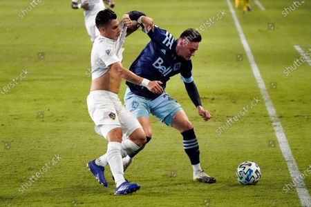 Vancouver Whitecaps's Jake Nerwinski, right, works against Los Angeles Galaxy's Cristian Pavon during the first half of an MLS soccer match, in Carson, Calif