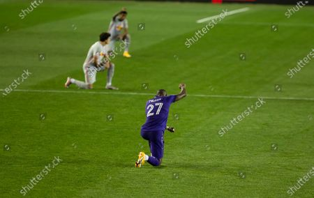 Kamal Miller (27) of Orlando City SC kneels and holds raised fist in honor of Black Lives Matter movement before regular MLS game against Red Bulls at Red Bull Arena. Game ended in draw 1 - 1. Game was played without fans because of COVID-19 pandemic precaution. All supporting staff and players on the bench were wearing facial masks and kept social distances.