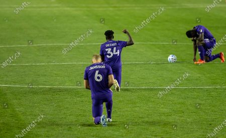 Joey Dezart (34) of Orlando City SC kneels and holds raised fist in honor of Black Lives Matter movement before regular MLS game against Red Bulls at Red Bull Arena. Game ended in draw 1 - 1. Game was played without fans because of COVID-19 pandemic precaution. All supporting staff and players on the bench were wearing facial masks and kept social distances.