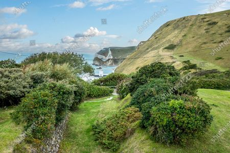 Stock Image of The view along the Jurassic Coast towards Durdle Door.   An impressive cliff-top home where Laurence Olivier honeymooned is on the market for £1.75m.  Weston is in an outstanding coastal position, in Lulworth Cove, Dorset, with views of the popular Durdle Door beauty spot, as well as Weymouth Bay, Portland and the Purbecks.  The Grade II listed house was designed by Sir Edwin Lutyens and is thought to be the only example of his work in Dorset.  The seven-bedroom property was built in the 1920s and is now in need of some refurbishment and modernisation.