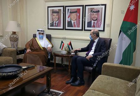 Jordanian Foreign Minister Ayman Safadi, right, meets with his Kuwaiti counterpart Sheikh Ahmad Nasser al-Mohammad al-Sabah, in Amman, Jordan, . Photos on wall show King Abdullah II, his father the late King Hussain, left, and Crown Prince Hussain