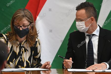 Hungarian Minister of Foreign Affairs and Trade Peter Szijjarto (R) and Bulgarian Deputy Prime Minister and Minister of Foreign Affairs Ekaterina Zaharieva (L) sign a document on the occasion of the 100th anniversary of the establishment of diplomatic relations between Hungary and Bulgaria in Budapest, Hungary, 19 October 2020.