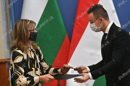 Hungarian Minister of Foreign Affairs and Trade Peter Szijjarto (R) and Bulgarian Deputy Prime Minister and Minister of Foreign Affairs Ekaterina Zaharieva (L) exchange documents after signing them on the occasion of the 100th anniversary of the establishment of diplomatic relations between Hungary and Bulgaria in Budapest, Hungary, 19 October 2020.