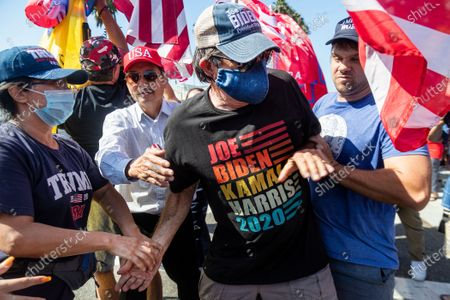 Biden supporter Richard Williams, 70, of Irvine is grabbed and shoved by Trump supporters as tried to hold his Biden-Harris sign though a sea of Trump supporters who gathered on Via Lido to get a glimpse of the president's motorcade while going to and from a fundraiser on Lido Island on October 18, 2020 in Newport Beach, California. (Gina Ferazzi / Los Angeles Times)