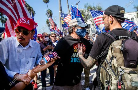 Stock Image of Biden supporter Richard Williams, 70, of Irvine, middle, is grabbed and shoved by Trump supporters as tried to hold his Biden-Harris sign though a sea of Trump supporters who gathered on Via Lido to get a glimpse of the president's motorcade while going to and from a fundraiser on Lido Island on October 18, 2020 in Newport Beach, California. (Gina Ferazzi / Los Angeles Times)