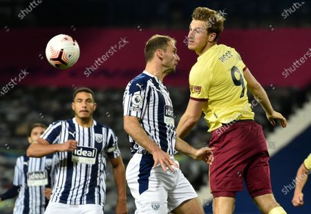 Burnley's Chris Wood, right, and West Brom's Branislav Ivanovic attempt to head the ball during the during the English Premier League soccer match between West Bromwich Albion and Burnley at the Hawthorns in West Bromwich, England