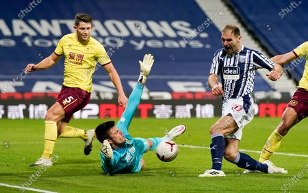 Burnley's goalkeeper Nick Pope blocks a shot from West Brom's Branislav Ivanovic, right, during the English Premier League soccer match between West Bromwich Albion and Burnley at the Hawthorns in West Bromwich, England