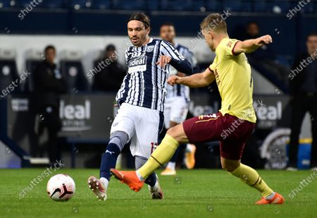 West Brom's Filip Krovinovic, left, battles for the ball with Burnley's Johann Berg Gudmundsson during the English Premier League soccer match between West Bromwich Albion and Burnley at the Hawthorns in West Bromwich, England