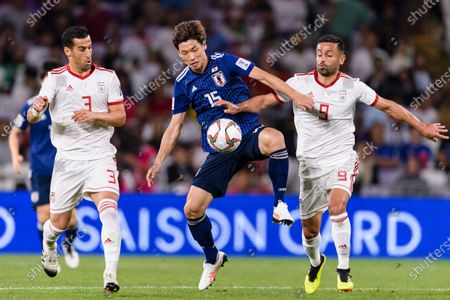 Osako Yuya of Japan (C) fights for the ball with Omid Ebrahimi Zarandini of Iran (R) and Ehsan Haji Safi of Iran (L) during the Semi Finals match