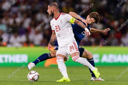 Seyed Ashkan Dejagah of Iran (L) fights for the ball with Osako Yuya of Japan (R) during the Semi Finals match
