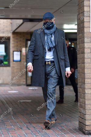 John L Stott better known as John Leslie wearing a face mask leaves Southwark Crown Court in London today after being found not guilty of groping a women's breasts at a party in 2008