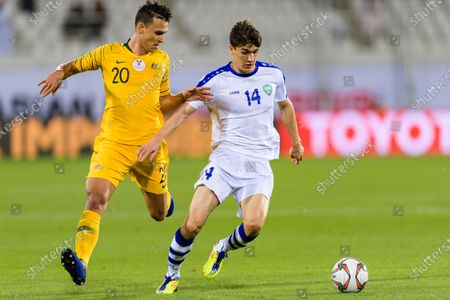 Eldor Shomurodov of Uzbekistan (R) fights for the ball with Trent Sainsbury of Australia (L) during the Round of 16 match