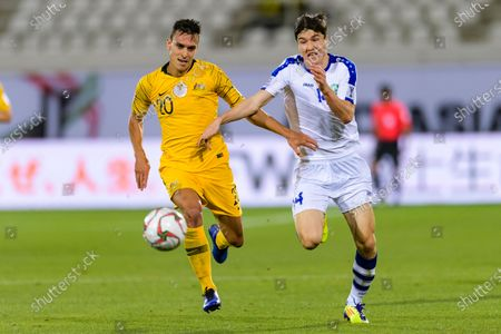 Trent Sainsbury of Australia (L) fights for the ball with Eldor Shomurodov of Uzbekistan (R) during the Round of 16 match