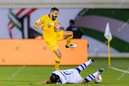 Aziz Behich of Australia (top) fights for the ball with Davronbek Khashimov of Uzbekistan (bottom) during the Round of 16 match