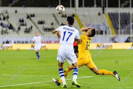 Aziz Behich of Australia (R) fights for the ball with Dostonbek Khamdamov of Uzbekistan (R) during the Round of 16 match