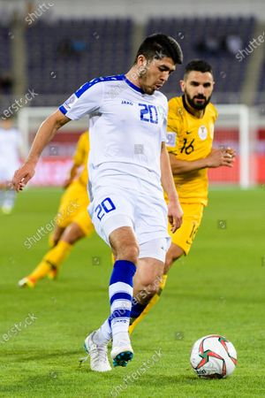 Islom Tukhtakhujaev of Uzbekistan (L) fights for the ball with Aziz Behich of Australia (R) during the Round of 16 match