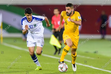 Aziz Behich of Australia (R) fights for the ball with Dostonbek Khamdamov of Uzbekistan (L) during the Round of 16 match