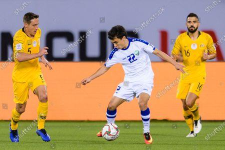 Javokhir Sidikov of Uzbekistan (C) fights for the ball with Mark Milligan of Australia (L) ad Aziz Behich of Australia (R) during the Round of 16 match
