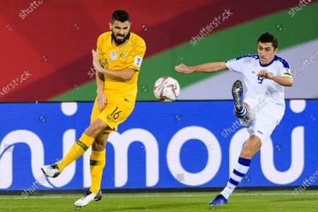 Odil Akhmedov of Uzbekistan (R) fights for the ball with Aziz Behich of Australia (C) during the Round of 16 match