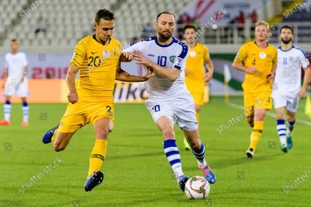 Trent Sainsbury of Australia (L) fights for the ball with Marat Bikmaev of Uzbekistan (C) during the Round of 16 match