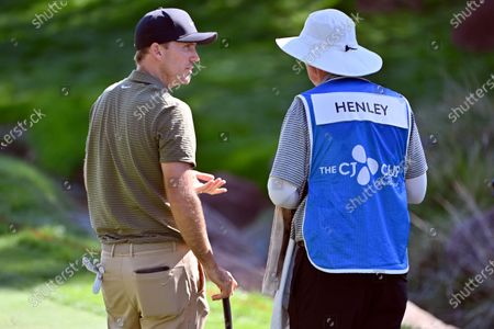 Russell Henley, left, speaks with his caddie during the final round of the CJ Cup golf tournament at Shadow Creek Golf Course, in North Las Vegas