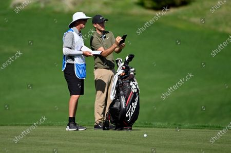 Russell Henley, right, speaks with his caddie during the final round of the CJ Cup golf tournament at Shadow Creek Golf Course, in North Las Vegas