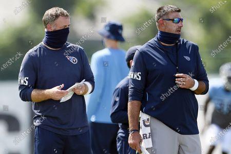 """Tennessee Titans outside linebackers coach Shane Bowen, left, and head coach Mike Vrabel watch players during NFL football training camp in Nashville, Tenn. The NFL and the NFL Players Association found instances when the Titans failed to wear masks at all times and were """"insufficiently clear"""" to players about not meeting or working out once the facility closed in a review given to the team, a person familiar with the investigation told The Associated Press. But the person familiar with the review says there was no discussion of any discipline for an individual including general manager Jon Robinson, coach Mike Vrabel or any players, and there was no discussion of punishment, including forfeitures or draft picks"""