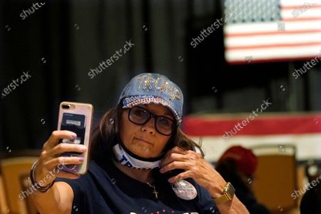 Supporter pulls down her mask to take a selfie prior to an address by Eric Trump, son of President, Donald Trump, at a campaign rally, in Manchester, N.H