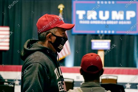 Masked supporter arrives for an address by Eric Trump, son of President, Donald Trump, prior to a campaign rally, in Manchester, N.H