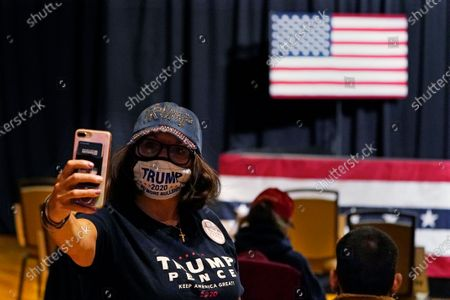 Stock Picture of Masked supporter takes a selfie as she waits for Eric Trump, son of President, Donald Trump, to arrive at a campaign rally, in Manchester, New Hampshire