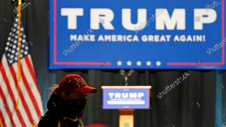 Masked supporter waits for Eric Trump, son of President, Donald Trump, to arrive at a campaign rally, in Manchester, New Hampshire