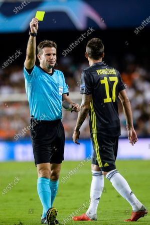 Stock Picture of Mario Mandzukic of Juventus (R) gets a yellow card from Mark Clattenburg FIFA referee (L) during their UEFA Champions League 2018-19 match between Valencia CF and Juventus FC at Estadio de Mestalla