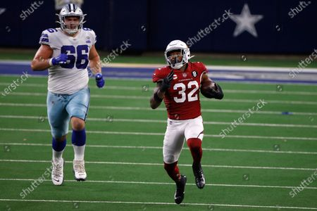 Dallas Cowboys guard Connor McGovern (66) gives chase as Arizona Cardinals' Budda Baker (32) returns an Andy Dalton (14) interception in the second half of an NFL football game in Arlington, Texas