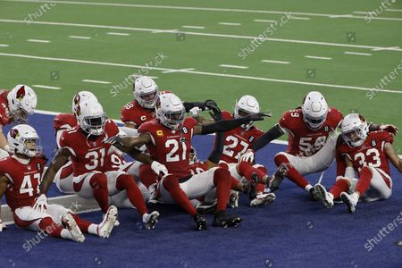 Members of the Arizona Cardinals defense act out a bowling pin strike dramatization after being hit by a ball rolled by Byron Murphy Jr. who intercepted a Dallas Cowboys quarterback Andy Dalton pass in the second half of an NFL football game in Arlington, Texas