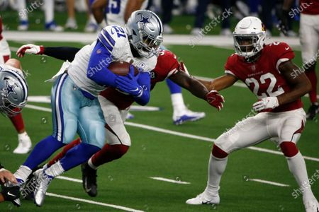 Dallas Cowboys running back Ezekiel Elliott (21) looks for running room against Arizona Cardinals' De'Vondre Campbell, rear, and Deionte Thompson (22) in the second half of an NFL football game in Arlington, Texas