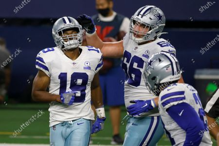Dallas Cowboys' Amari Cooper (19) is congratulated by Connor McGovern (66) on Cooper's touchdown catch in the second half of an NFL football game against the Arizona Cardinals in Arlington, Texas