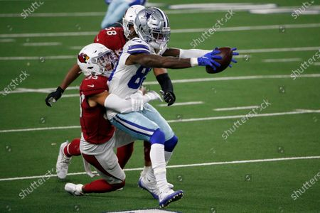 Dallas Cowboys wide receiver CeeDee Lamb (88) catches a pass for a first down as Arizona Cardinals' Byron Murphy Jr. (33) and Jordan Hicks (58) combine to make the stop in the second half of an NFL football game in Arlington, Texas