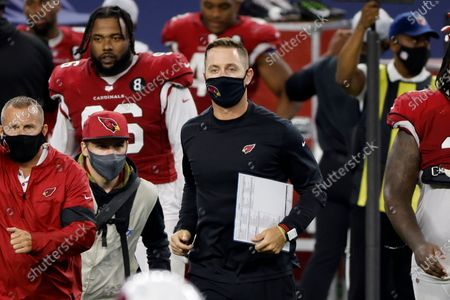 Arizona Cardinals head coach Kliff Kingsbury, center in black, jogs onto the field after their 38-10 win against the Dallas Cowboys in an NFL football game in Arlington, Texas
