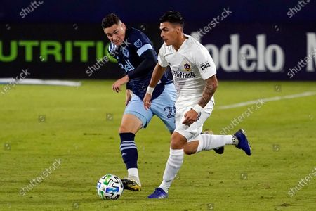 Los Angeles Galaxy's Cristian Pavon, right, dribbles past Vancouver Whitecaps's Jake Nerwinski during the first half of an MLS soccer match, in Carson, Calif