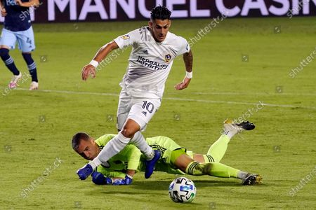 Los Angeles Galaxy's Cristian Pavon, top, has his shot deflected by Vancouver Whitecaps goalkeeper Evan Bush during the first half of an MLS soccer match, in Carson, Calif
