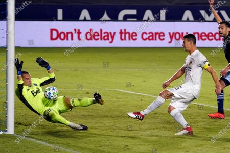 Stock Photo of Vancouver Whitecaps goalkeeper Evan Bush, left, stops a shot from Los Angeles Galaxy's Daniel Steres during the first half of an MLS soccer match, in Carson, Calif