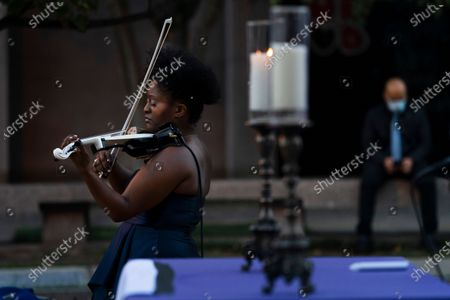 """Violinist Melanie Hill performs during the """"Mourning Into Unity"""" vigil, on a section of 16th Street that has been renamed Black Lives Matter Plaza, near the White House in Washington. Washington's Church of the Epiphany hosted a national candlelight vigil where hundreds of feet of purple fabric symbolizing mourning during COVID-19 was unfurled"""
