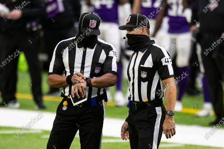Back judge Greg Meyer (78), left, talks to line judge Tim Podraza (47) in the first quarter during an NFL football game between the Atlanta Falcons and Minnesota Vikings, in Minneapolis. The Falcons defeated the Vikings 40-23