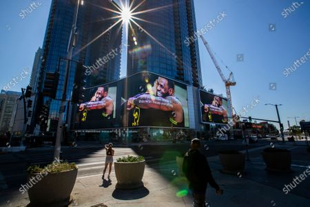 Pedestrians paus to view giant video screens featuring Lakers champions LeBron James and Anthony Davis hugging at the Circa apartment complex across the street from the Staples Center, where fans were gathering to celebrate the morning after the Lakers championship win on Monday, Oct. 12, 2020 in Los Angeles, CA. (Allen J. Schaben / Los Angeles Times)