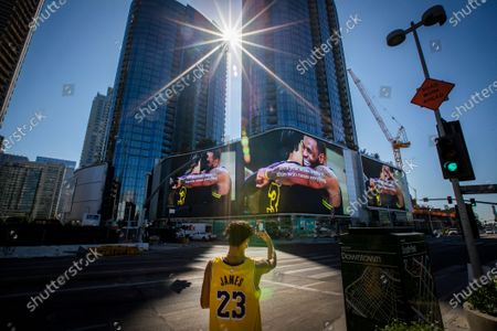 """Lakers fan Michael Vasquez, of Buena Park, takes video of giant video screens featuring Lakers champions LeBron James and Anthony Davis hugging at the Circa apartment complex across the street from the Staples Center, where fans were gathering to celebrate after the Lakers championship win on Monday, Oct. 12, 2020 in Los Angeles, CA. """"This is my city, my team and we had to do it for Kobe,"""" Vasquez said. """"With all this COVID, we really needed this. It's a blessing. After Kobe dying it just brings the city together all as one."""" (Allen J. Schaben / Los Angeles Times)"""
