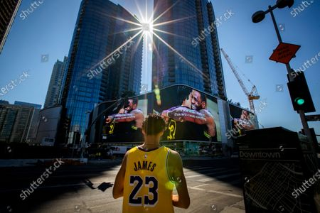 """Lakers fan Michael Vasquez, of Buena Park, views giant video screens featuring Lakers champions LeBron James and Anthony Davis hugging at the Circa apartment complex across the street from the Staples Center, where fans were gathering to celebrate after the Lakers championship win on Monday, Oct. 12, 2020 in Los Angeles, CA. """"This is my city, my team and we had to do it for Kobe,"""" Vasquez said. """"With all this COVID, we really needed this. It's a blessing. After Kobe dying it just brings the city together all as one."""" (Allen J. Schaben / Los Angeles Times)"""