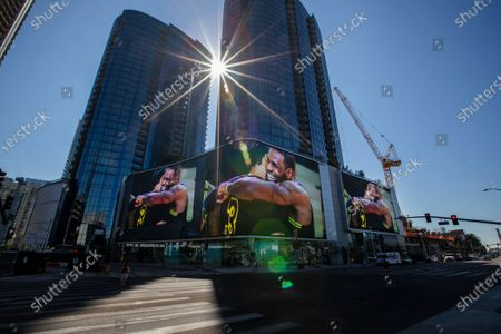 The sun shines down on giant video screens featuring Lakers champions LeBron James and Anthony Davis hugging at the Circa apartment complex across the street from the Staples Center, where fans were gathering to celebrate the morning after the Lakers championship win on Monday, Oct. 12, 2020 in Los Angeles, CA. (Allen J. Schaben / Los Angeles Times)