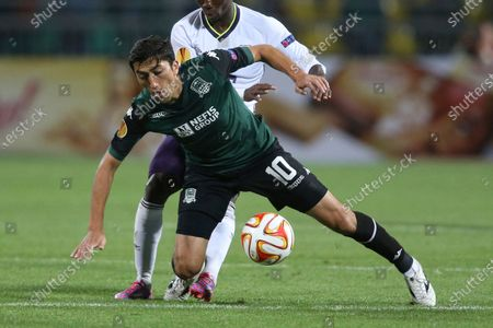 Krasnodar's Odil Ahmedov, front, fights for the ball with Everton's Christian Atsu during the Europa League Group H soccer match between Krasnodar and Everton in Krasnodar, Russia. In a bid to complete the 2020 season in the midst of restrictions caused by the COVID-19 pandemic, the Chinese Football Association decided to split the 16 top-tier CSL teams into two groups based in the hub cities of Dalian and Suzhou